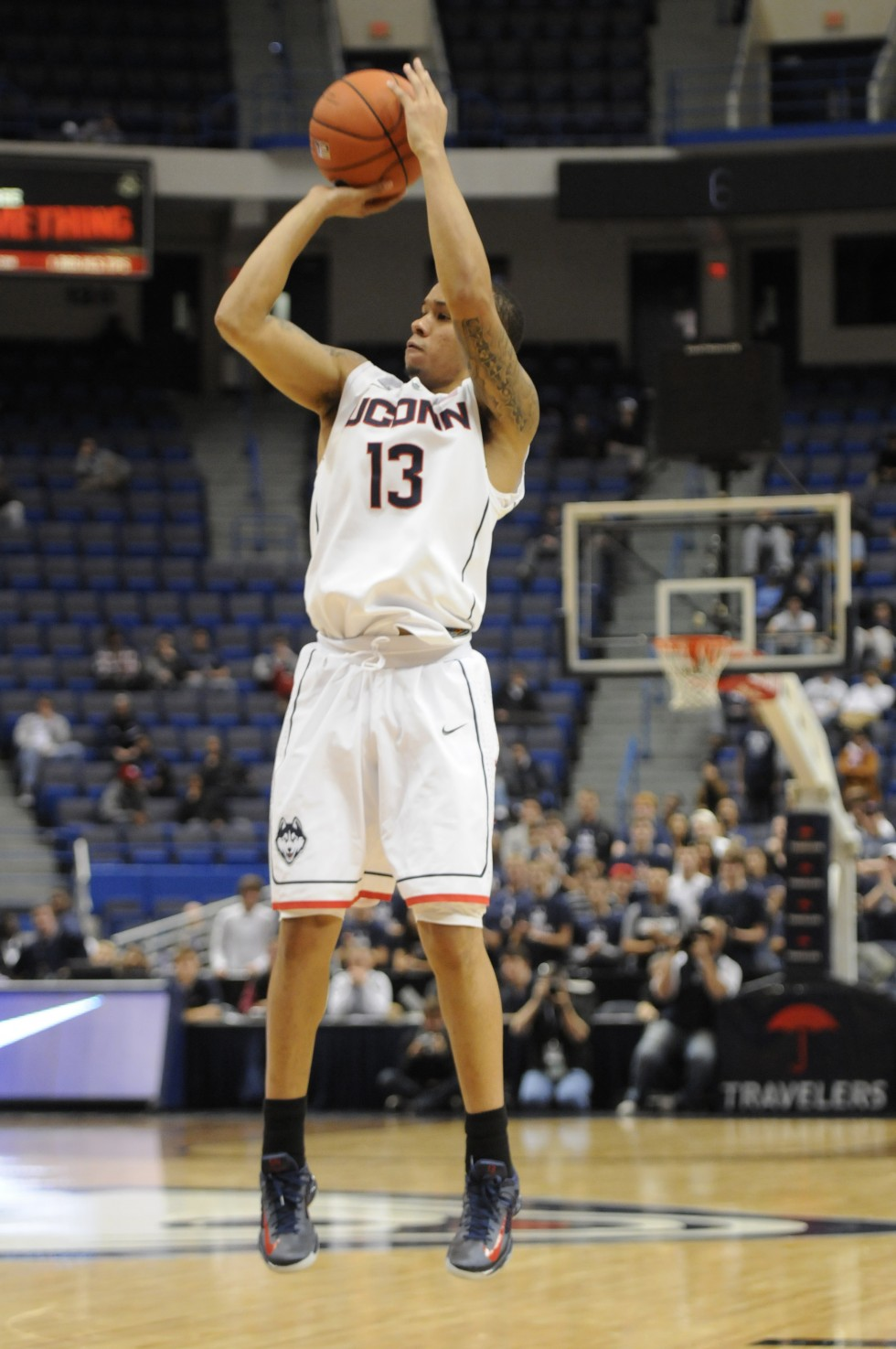 Huskies Senior guard Shabazz Napier, 13, makes a there point basket late in the second half.