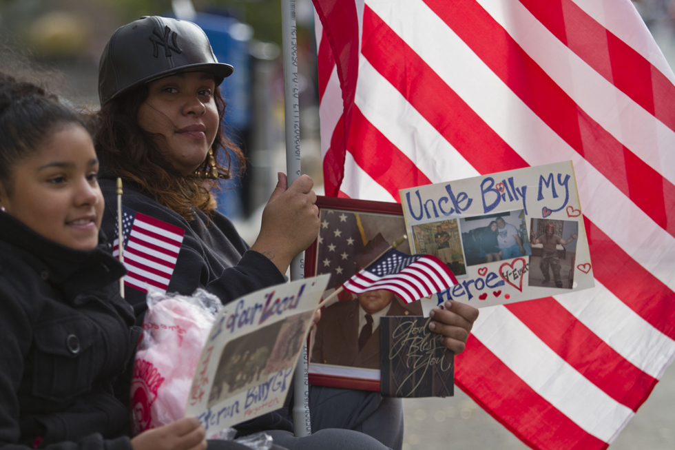 Relatives honor a family members while watching the CT Veteran's Parade wind its way through downtown Hartford. Johnathon Henninger|Special to the Courant.