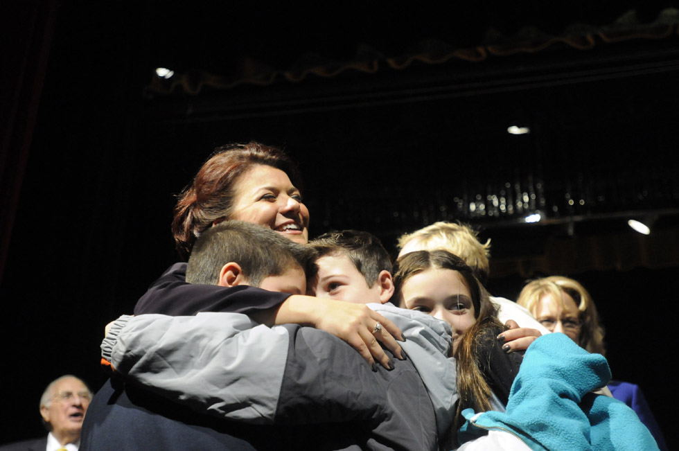 New Britain Mayor Erin Stewart embraces, from left, Benjamin, 8, Nicholas, 12 and Morgan Giantonio, 11, right, on stage at New Britain High School after she was sworn in Tuesday. They are the children of Common Council member Jamie Giantonio.