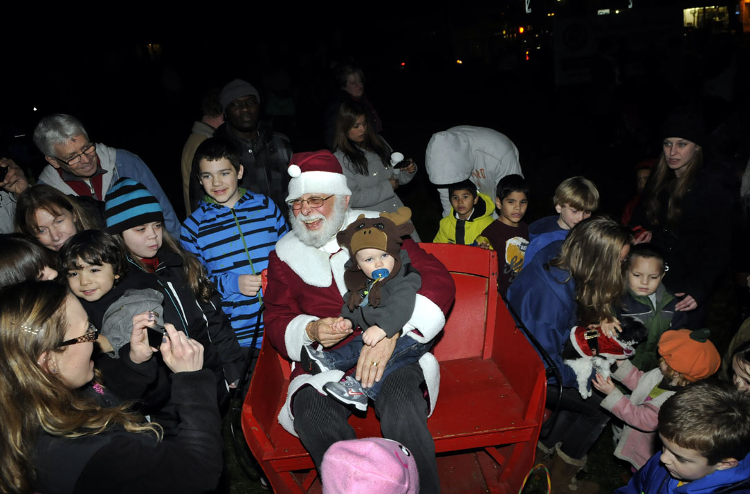 The highlight of the annual Christmas Tree lighting ceremony on Main Street in Manchester is the arrival of Santa Claus who is also known as George Ducharme, an adjunct professor at Manchester Community College. Sitting in his lap is Myles Moynihan, 14 mos, of Manchester.