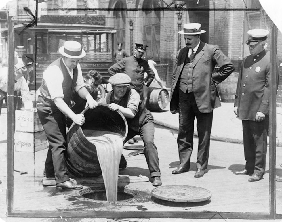 New York City Deputy Police Commissioner John A. Leach (R) watches agents pour liquor into a sewer following a raid during the height of prohibition in an undated photo held by the Library of Congress. REUTERS/Library of Congress/Handout via Reuters