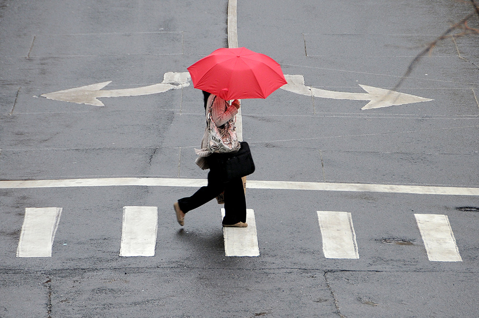 HARTFORD 04/12/13 A woman with a red umbrella crosses Temple Street in the rain in downtown Hartford Friday afternoon. Friday's cool rainy weather should give way to more spring-like temperatures this weekend. CLOE POISSON | cpoisson@courant.com