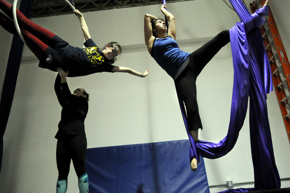 Darcy Jeffrey, left, gets some help in the Lyra aerial hoop and Catherine Pahdi, a Yale Sr., works out on the silks.