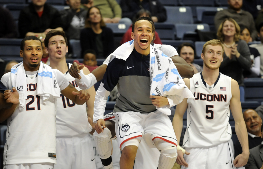 Shabazz Napier leads his teammates in a cheer as they watched the bench players try to score at the end of the game. From left, Omar Calhoun, Tyler Olander, Napier and Niels Giffey. Napier was game-high scorer with 19 pts.