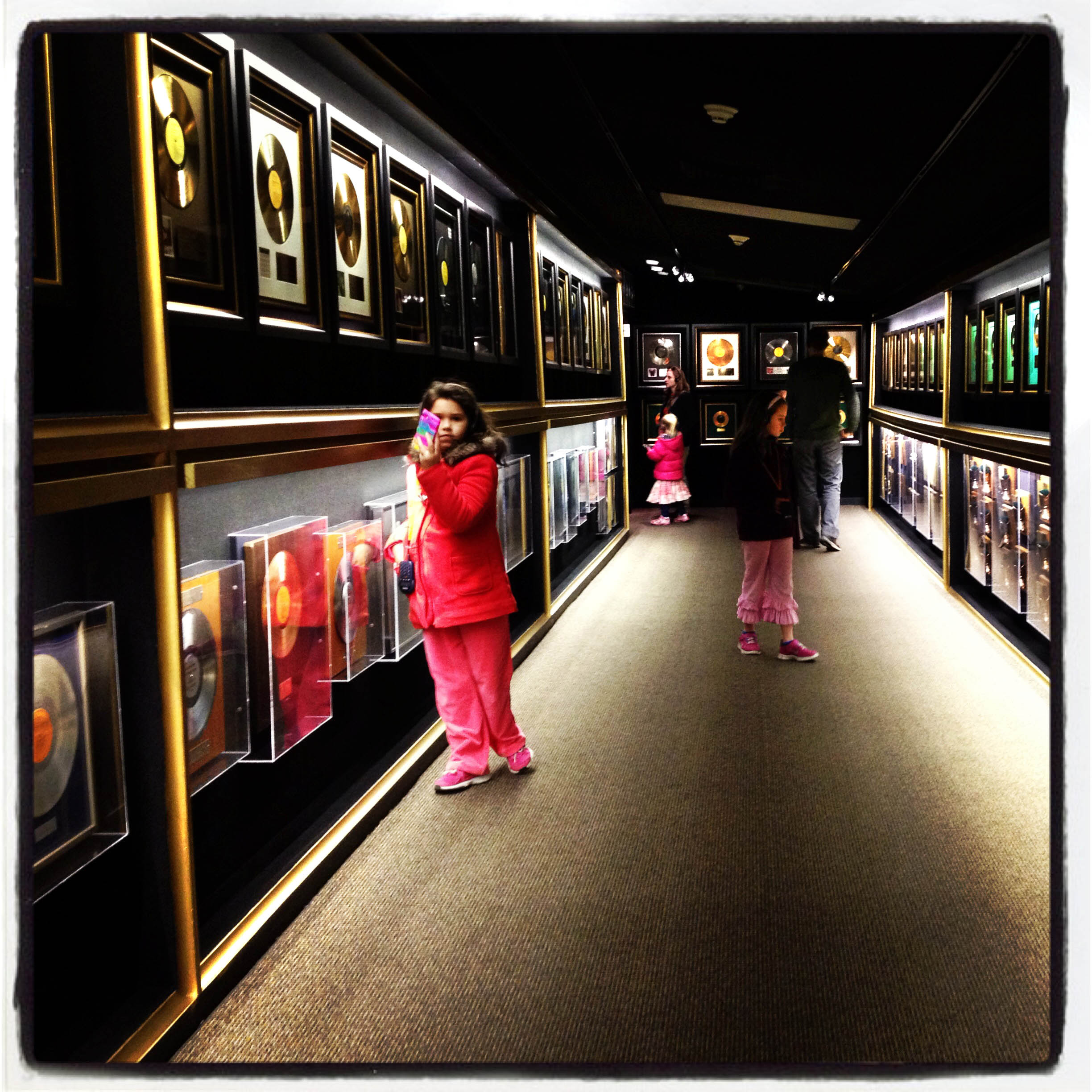 MEMPHIS, TN 01/03/14 A young girl takes a photo with her cell phone in the Trophy Room at Graceland. The room is filled with gold and platinum records and awards from around the world.  Presley had 18 number one hits. CLOE POISSON|cpoisson@courant.com