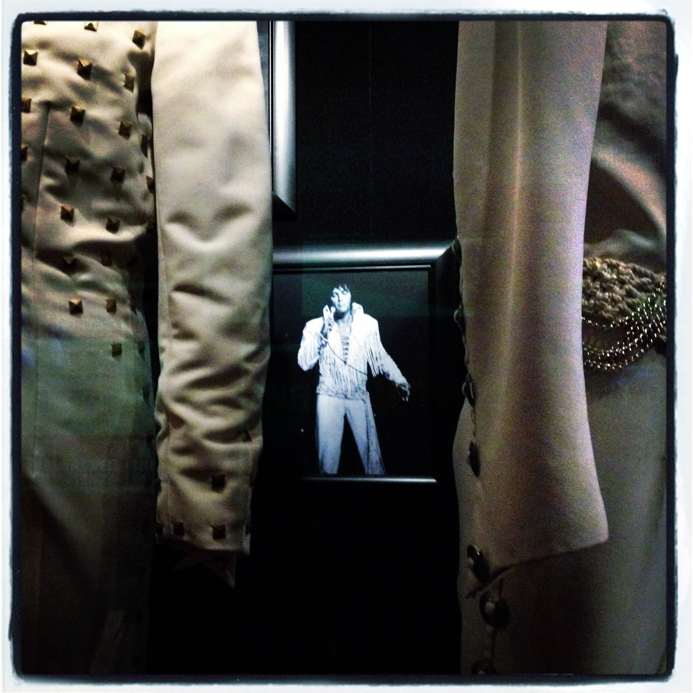 MEMPHIS, TN 01/03/14 A ghost-like image of Elvis is visible between two of his famous white studded performance outfits at Graceland. CLOE POISSON|cpoisson@courant.com