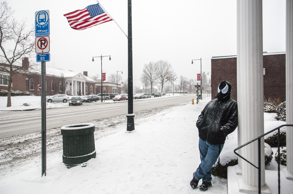 2014.01.02. - Manchester, CT - Braving today's snow with a Spiderman hoodie, 20-year-old Damon Gagnon of Manchester waits on Main Street for a bus to take him to his job at the Funny Bone Comedy Club. Photograph by Mark Mirko | mmirko@courant.com