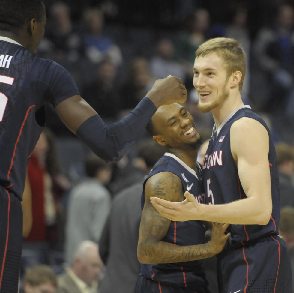 From left, University of Connecticut Huskies center Amida Brimah, 35, University of Connecticut Huskies guard Ryan Boatright, 11, and University of Connecticut Huskies guard/forward Niels Giffey, 5,  react after the game.
