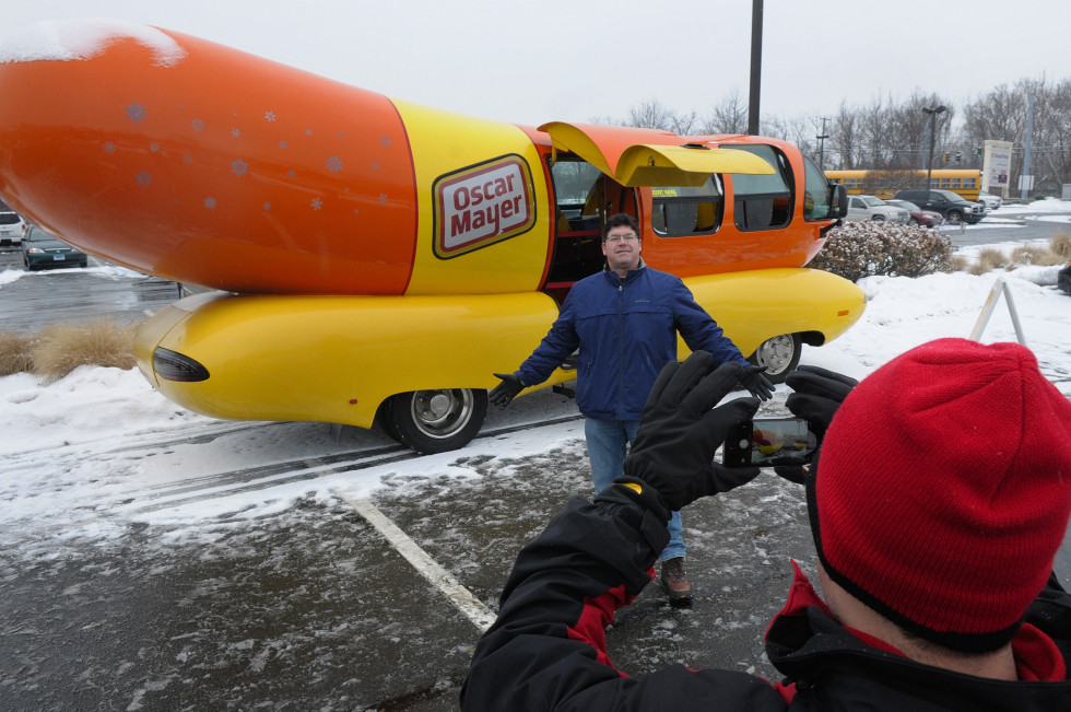 Russell Guerin, of West Hartford, gets his photo taken by Sam Blum, one of the two drivers of the Wienermobile. Blum, of Maryland and a recent graduate of The University of Maryland, volunteered to use Guerin's own camera so he could have a souvenir of himself with the unique vehicle. Blum, a self described Hotdogger, works for Oscar Mayer, traveling the country and spreading brand awareness.