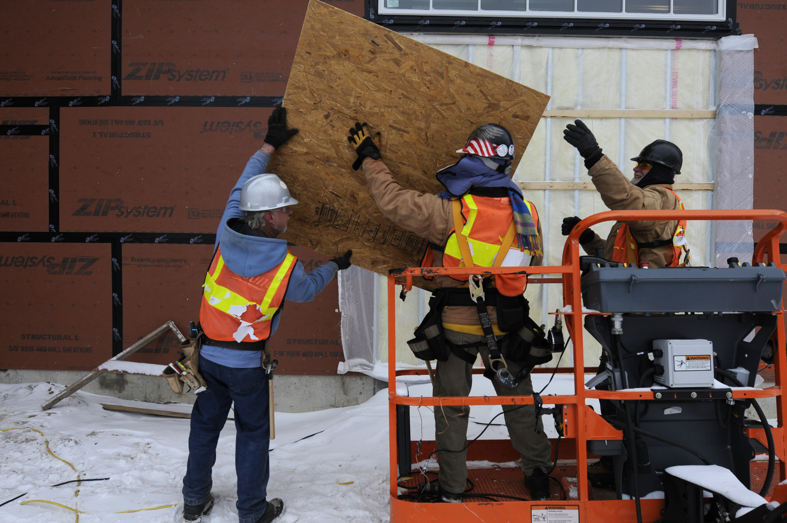 Brothers Gerry, Don and Rick Soucy load a sheet of plywood onto a lift while working in 16 degree weather at the Glastonbury boathouse construction site in Glastonbury Thursday. The three carpenters come prepared for the cold when working outside in winter.