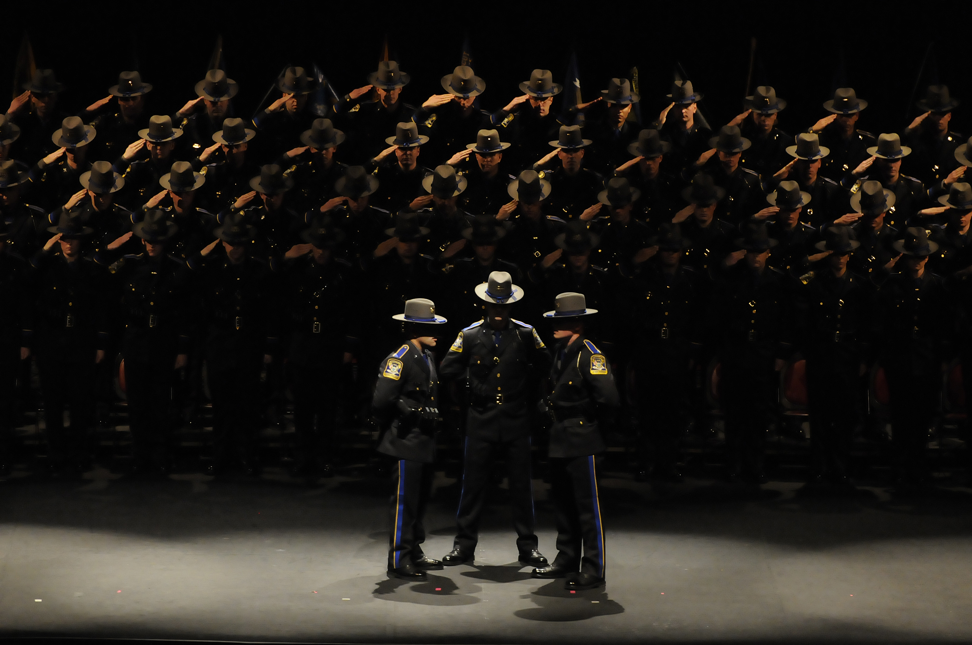 Connecticut State Police Trooper Trainees Alexander Cintron, Adam List and Gregory Sawicki sing the National Anthem at the start of the State Police 123rd Training Troop graduation at the University of Connecticut in Storrs Thursday. Eighty three graduated and will be patrolling the state.