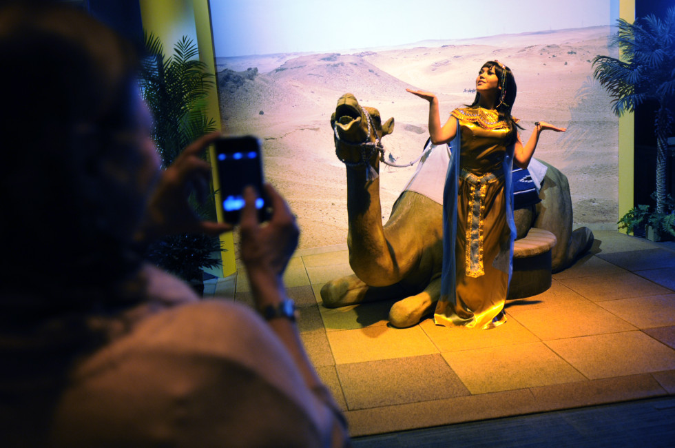 "Lexi Prieto, of Waterbury, playing the part of Cleopatra, poses for a visitors to take a photo in front of a model camel she called ""Sandy."" Preto, who works for Powerstation Events out of Cheshire, said she has done other events at the Science Center, but has never before played the part of Cleopatra."