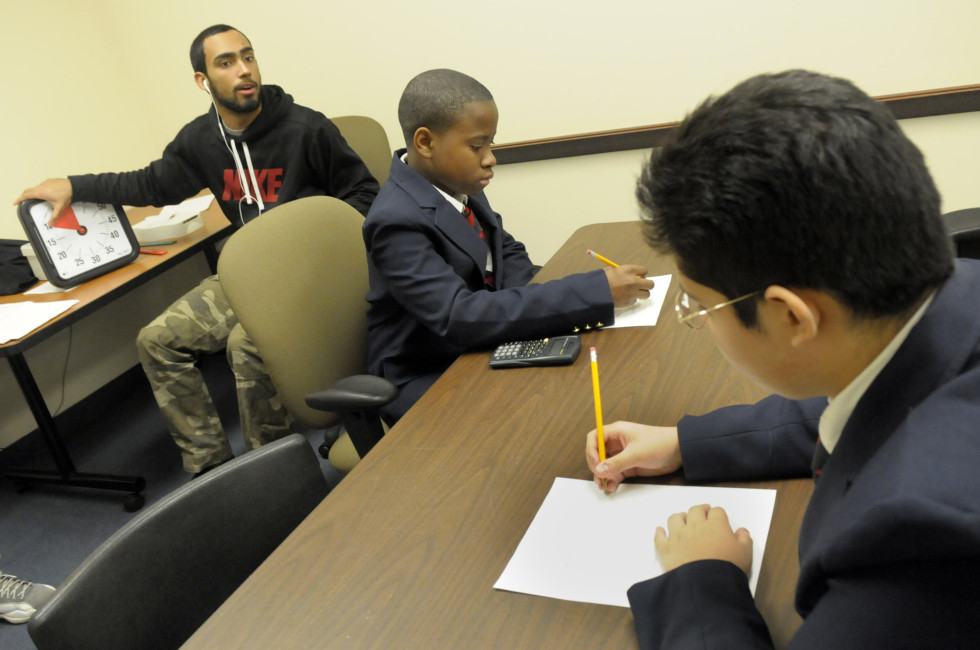 Bryan Figueroa, left, an alumni of Hartford Public, and on semester break, instructs the high school students during one of their morning competitions. Tajay Edwards, 14, center, and Sebastian Cerna, 14, both students at High School Inc., prepare to start their timed test.