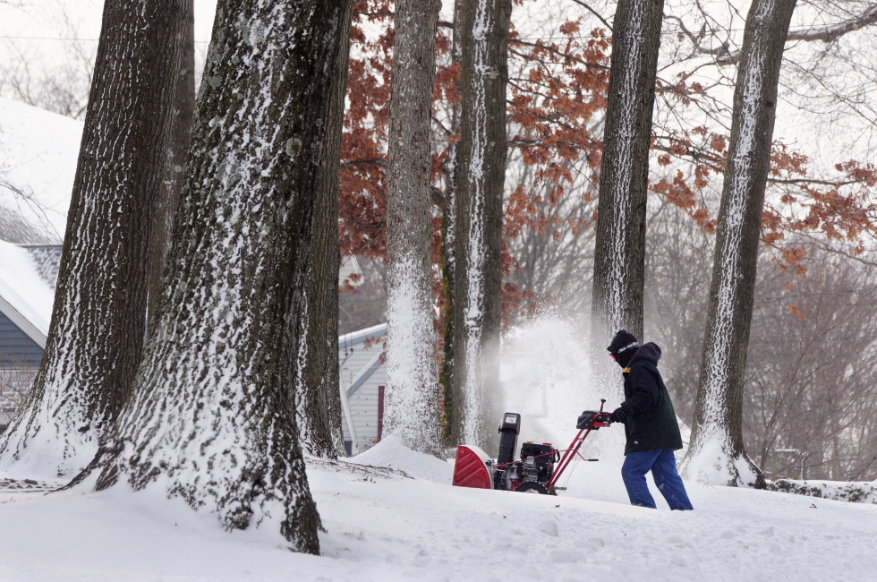 John Sassu clears the driveway of his Bristol home, as the wind works against him and also paints the trees white. The first storm of the new year hit Connecticut Thursday night and into Friday.