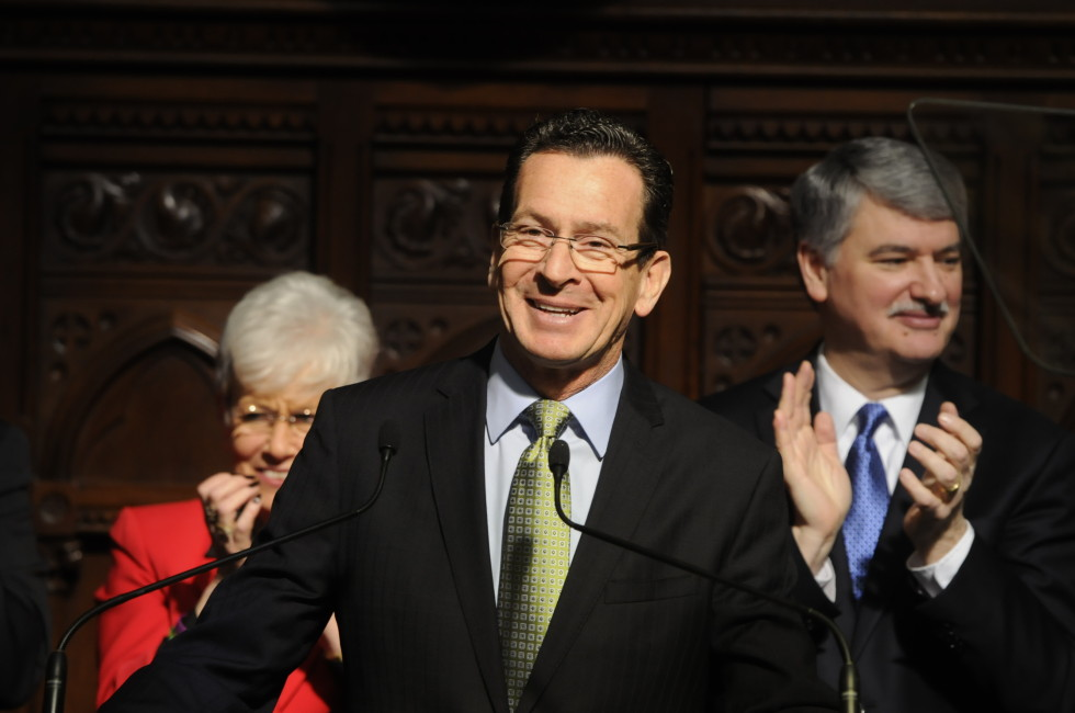 Gov. Dannel P. Malloy reacts to applause after being introduced to a joint senate-house session to present his state of the state address at the beginning of the snow-delayed 2014 legislative session on Thursday. Behind are Lieutenant Governor, Nancy Wyman, left, and Senetor and President Pro Tempore, Donald Williams.