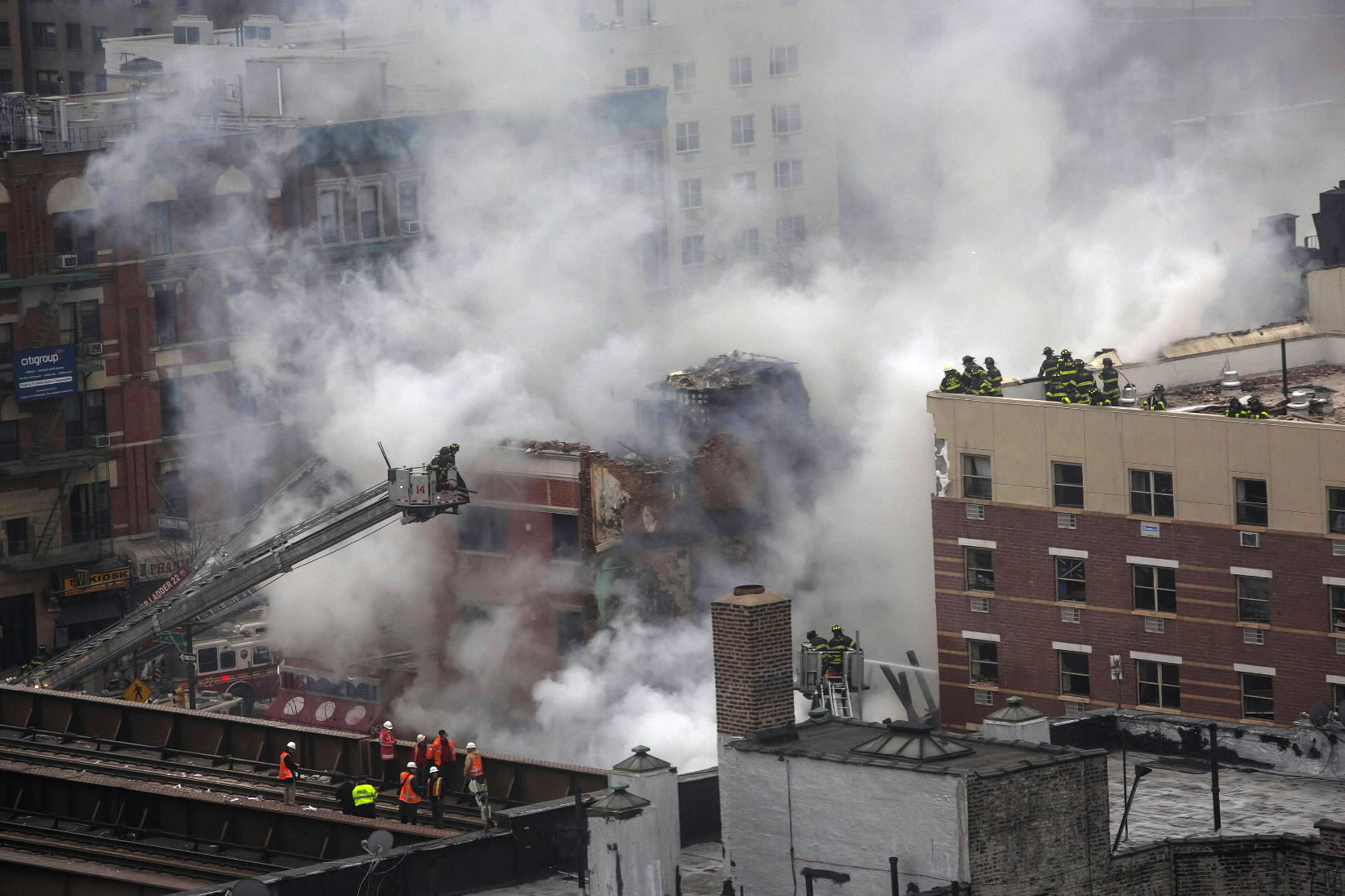 New York City firefighters examine the rubble at an apparent building explosion, fire and collapse in the Harlem section of New York, March 12, 2014. Two buildings collapsed in an explosion in Upper Manhattan on Wednesday, killing at least three, injuring at least 17 and setting off a search for anyone trapped in the debris, witnesses and officials said.