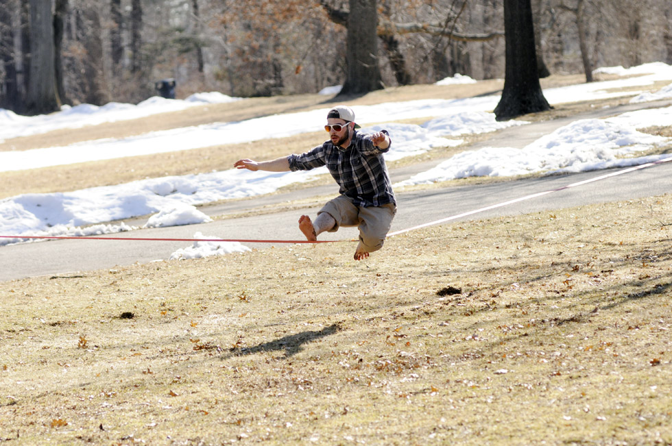 Zach McCulloch, 22, of Bloomfield walks a slackline between two trees Tuesday afternoon at Hartford's Elizabeth Park.