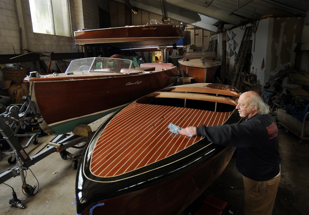 Boyd Mefferd wipes down a vintage 1942 19' Chris Craft barrel stern double cockpit mahogany runabout inside his shop. Mefferd's shop completely rebuilt the deck on the rare boat. At left is a 1950 22' Chris Craft Sportsman and at right is a classic Fay & Bowen 30' triple cockpit, one of only two ever built. On the rack above is Mefferd's own 1956 Chris Craft Sportsman.