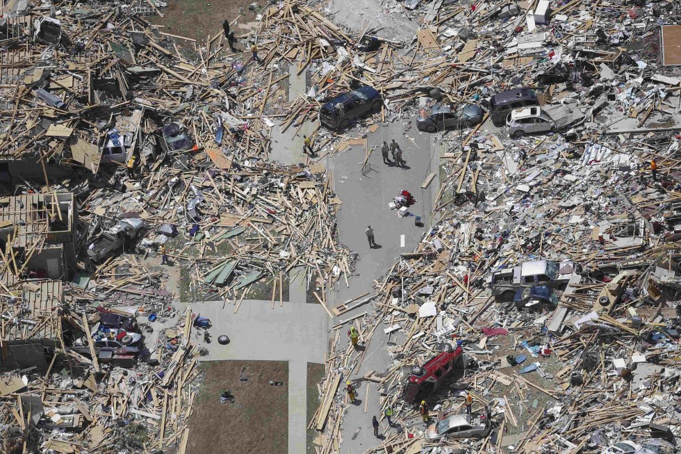 Rescue workers and volunteers stand amid debris of homes one day after they were destroyed by a tornado in Vilonia, Arkansas April 28, 2014. A ferocious storm system caused a twister in Mississippi and threatened tens of millions of people across the U.S. Southeast on Monday, a day after it spawned tornadoes that killed 16 people and tossed cars like toys in Arkansas and other states.  REUTERS/Carlo Allegri