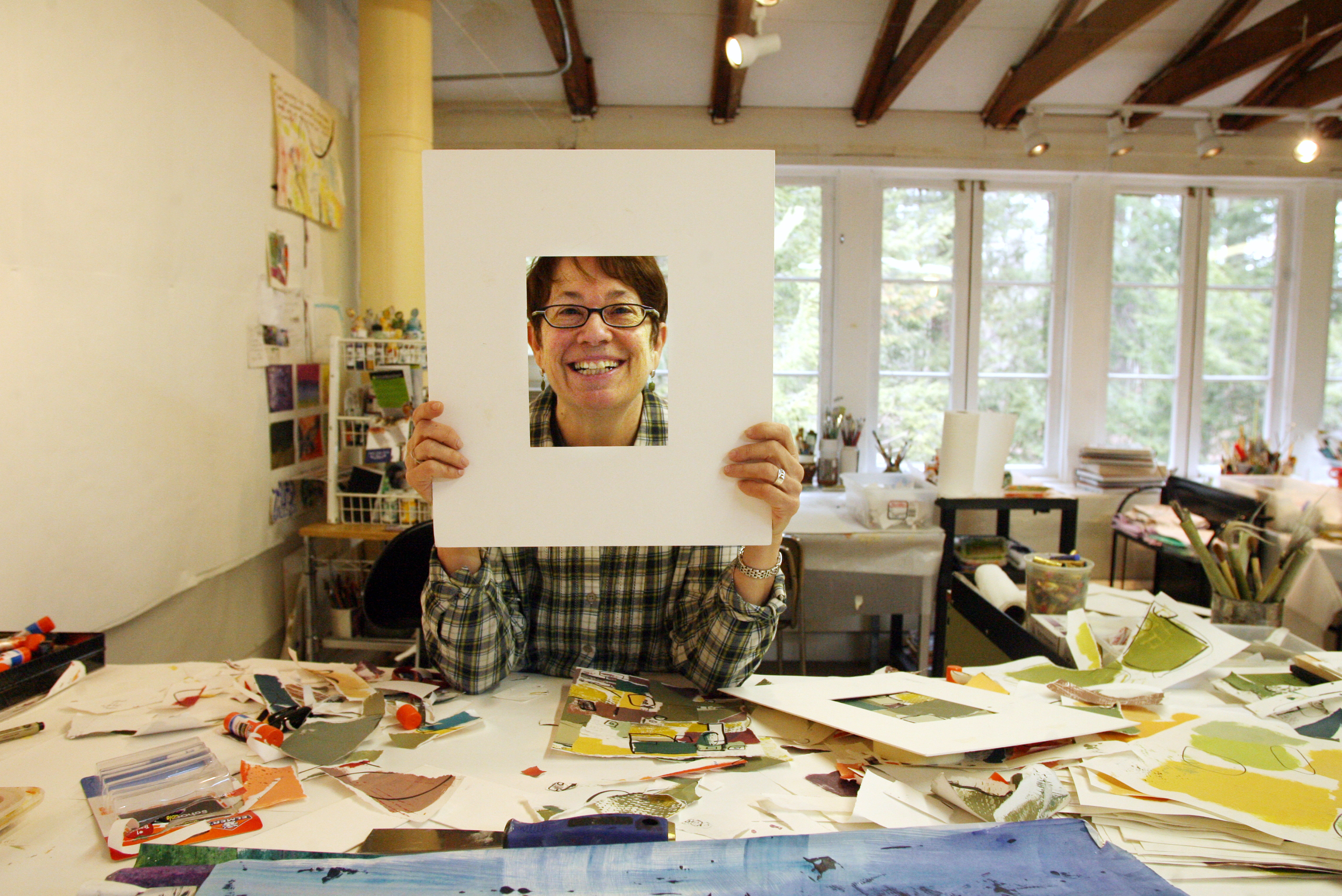 C. Dianne Zweig, a mixed media artist, uses collage to create abstract images in her studio at the Farmington Valley Arts Center.