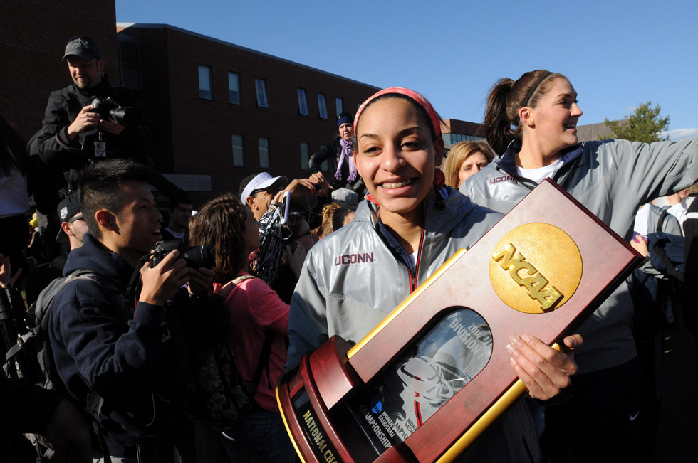 Senior Bria Hartley, left, carries the NCAA trophy through the crowd as the UConn Women returned to campus Wednesday afternoon. Behind her is Stefanie Dolson.