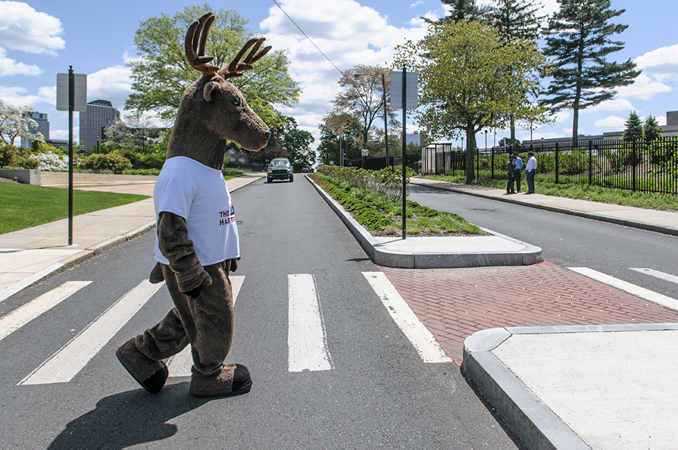 "05.19.2014 - Hartford, Ct - Dressed as ""Larry the Stag,"" mascot for The Hartford, Scott Bruzik, returns to his office at The Hartford after attending a free concert by the Hartford Symphony Brass Quintet. The event was attended by over 100 people including students from Trinity Episcopal Day School and Grace Academy Hartford. The free concert is one of two free concerts open to the public and hosted by The Hartford in HartBeat Park. The HSO String Quartet will perform June 4. Photograph by Mark Mirko 
