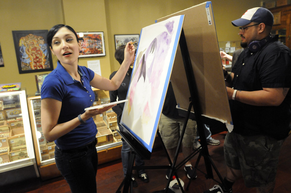 "Illustrator Chrissie Zullo, of New Haven, left, a guest artist at Hartford Comic Con, which is being held through June 1 at the XL Center in Hartford, turns to talk to a visitor at the Tobacco Shop on Pratt Street Friday night where she and fellow artist Christopher Uminga, also of New Haven, right, were making art to be displayed at the shop for the remainder of the show. She was doing a watercolor of ""Death,"" a character from the Sandman comic books. Other artists who were slated to make art at the shop were Jim Mahfood, Kaare Andrews and Dave Johnson. Artists also created comic art with cigar boxes which came from the shop. The  proceeds from the sale of the boxes, at $200 each, will go to the UConn migrant farmers clinic."