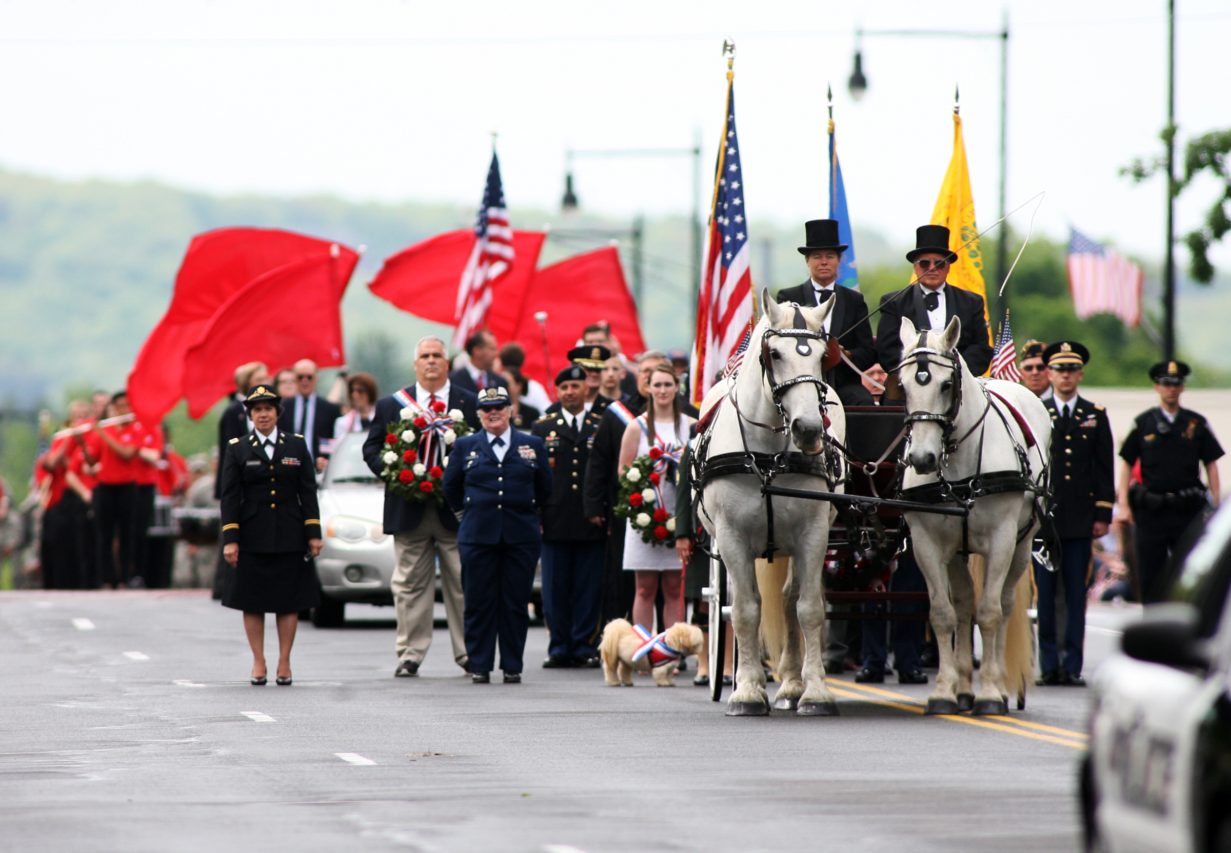 Dignitaries follow a horse drawn caisson carrying a casket representing war dead in Manchester's Memorial Day Parade Monday.