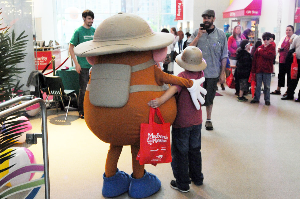 A dad takes his son's picture with Mr. Potato Head at Connecticut Science Center's Ribbon Cutting and preview of the new traveling exhibits Mindbender Mansion and The Adventures of MR. POTATO HEAD.