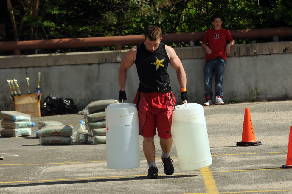 Adam Zamojski, 18, a junior at New Britain High, carries approximately 100 pounds of water in each hand during the annual Tough Man competiton fundraiser at New Britain High Thursday. Two student teams, a teacher team and the U.S. Marines competed.  Teams competed in strength and agility contests. Money raised goes toward equipment and other expenses for the J-Crew, a NBHS Bible club which is involved in mentoring and other community service activities.