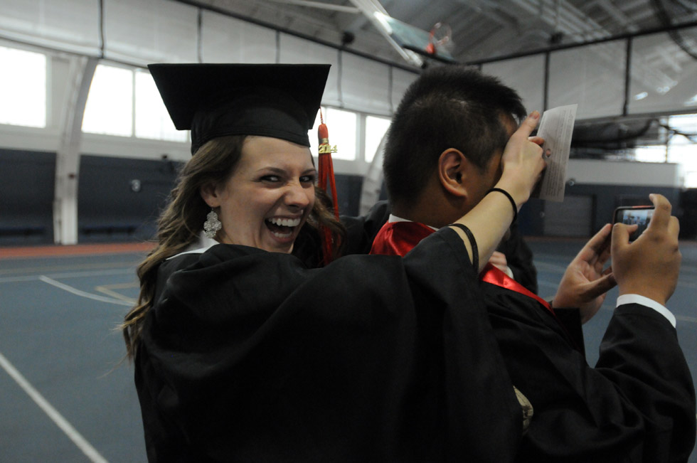 Meaghan Sullivan, of Dartmouth, Mass., at left, surprises friend Richard Baldio, of Salem, New Hampshire as he is about to take a picture of friends in the field house on the UConn campus Saturday morning as they waited for graduation exercises to begin.