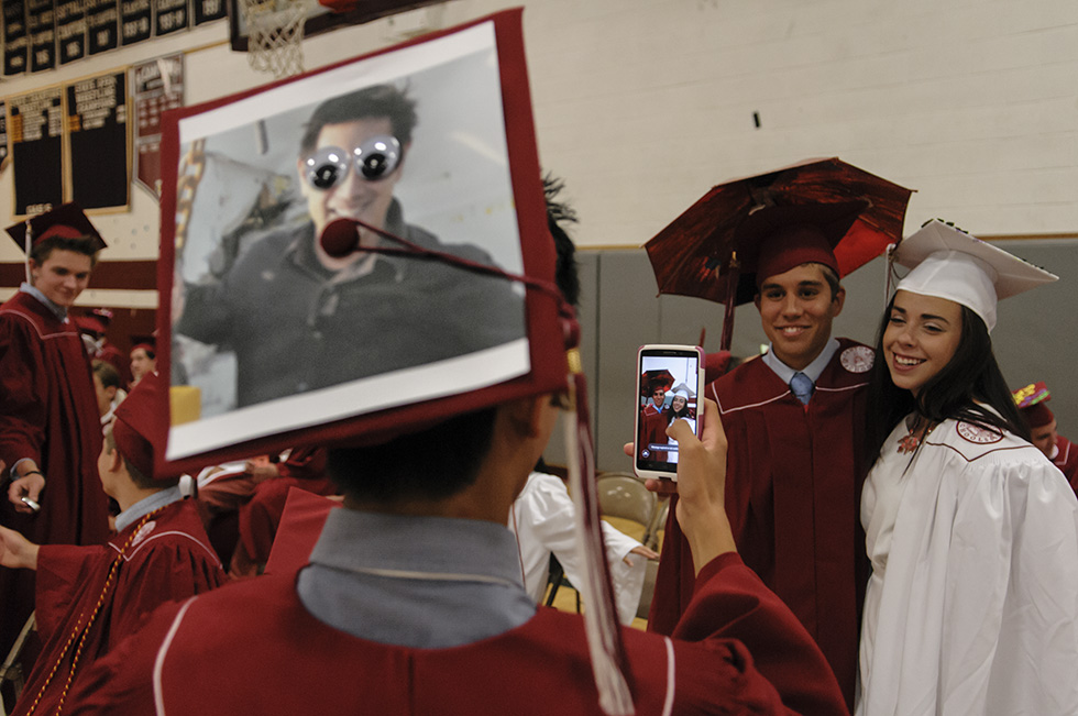 "06.20.2014 - Canton, Ct - With a photograph of Grant Imahara from ""Mythbuster"" on his cap, because ""people think I look like him,"" Canton High School student Wyatt Campbell photographs Athan Chekas and Dakota Bybee before Canton's graduation ceremony. . Photograph by Mark Mirko 
