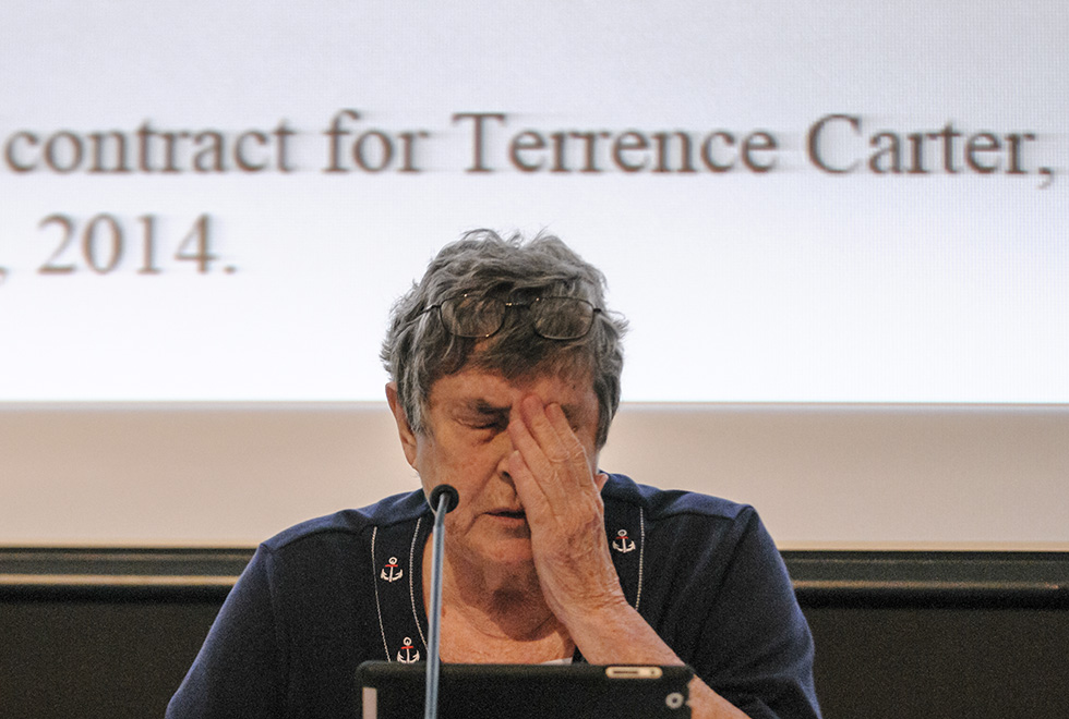 2014.07.24 - New London, Ct. - With an item from the evening's agenda projected on the screen behind her, New London Board of Education President Peg Curtin prepares to read a motion to hold off on deciding what to do about Terrence P. Carter until it the board can conduct its own investigation. At issue are charges that Carter falsified his resume that included crediting himself with an PhD. Photograph by Mark Mirko |mmirko@courant.com