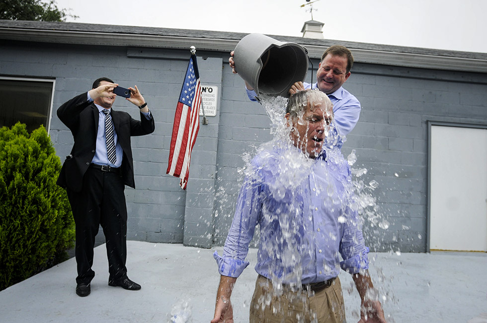 TRUMBULL 08/13/14 John McKinney pours a bucket of ice water on Republican candidate for governor, Tom Foley, after a press conference with John McKinney at Foley's campaign headquarters in Trumbull Wednesday morning.  McKinney challenged Foley to take the ALS challenge in which you agree to have a bucket of cold ice water poured on you or pay $100 to raise awareness of ALS. Foley took the challenge and agreed to pay the $100 as well. McKinney was challenged last night by one of his daughters after the Republican primary.  Foley will face incumbent Gov. Dannel Malloy in November. Trumbull first selectman Tim Herbst takes a photo at left.  CLOE POISSON|cpoisson@courant.com