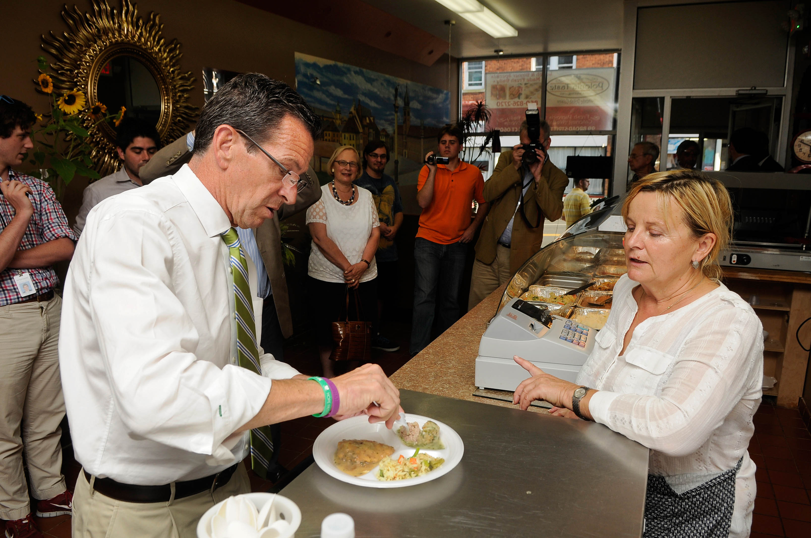 NEW BRITAIN 08/14/14 Gov. Dannel Malloy samples a Polish meatball with dill and chicken marsala with rice during a visit to Polonia Taste on Broad Street in New Britain Thursday evening as his reelection campaign gets underway. Malloy spent time visiting businesses along Broad Street in the city's Polish neighborhood. Bartkowicz mentioned that Malloy's Republican opponent, Tom Foley, also sampled the chicken Marsala and rice during a recent campaign visit..   CLOE POISSON|cpoisson@courant.com