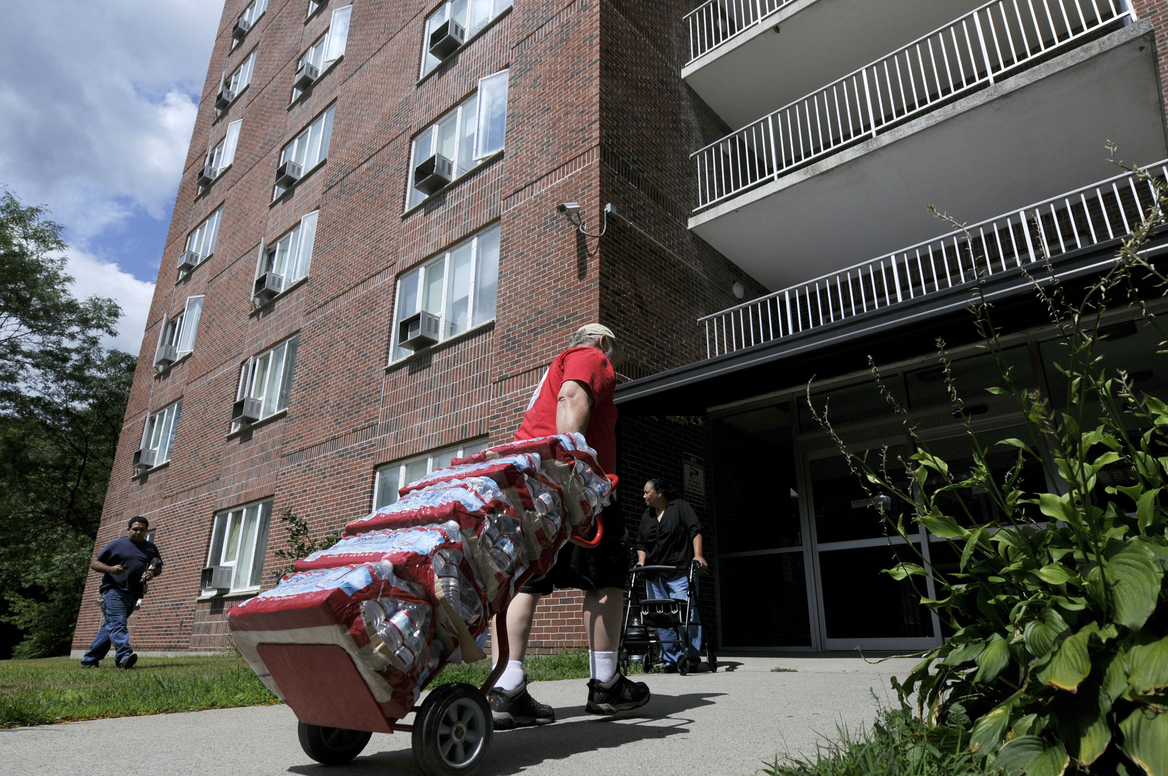 Several cases of bottled water are delivered to the New London Housing authority highrise on Colman Street by staff from the American Red Cross after residents lost water service Thursday. A water main break in New London's Bates Woods Park nearby caused lowered water pressure for some and interrupted service for others.
