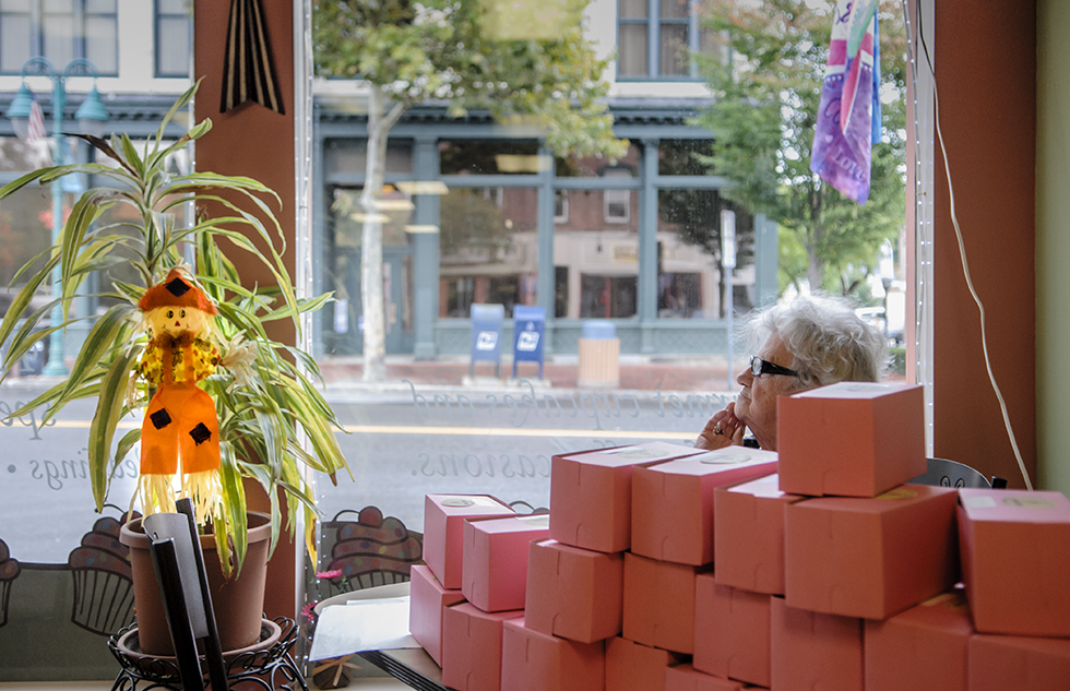 "09.25.2014 - Willimantic, Ct. - Alice Mott, 82, mother of Cheryl Preston, the owner of A Cupcake for Later, pauses while folding cupcake boxes in the window of her daughter's bakery. ""I Like to watch the people walk by. How they dress. What they do,"" she says about her view of Willimantic's Main Street. Mott, a lifelong resident of the area says she comes in to her daughter's shop to help out ""almost everyday."" Photograph by Mark Mirko 
