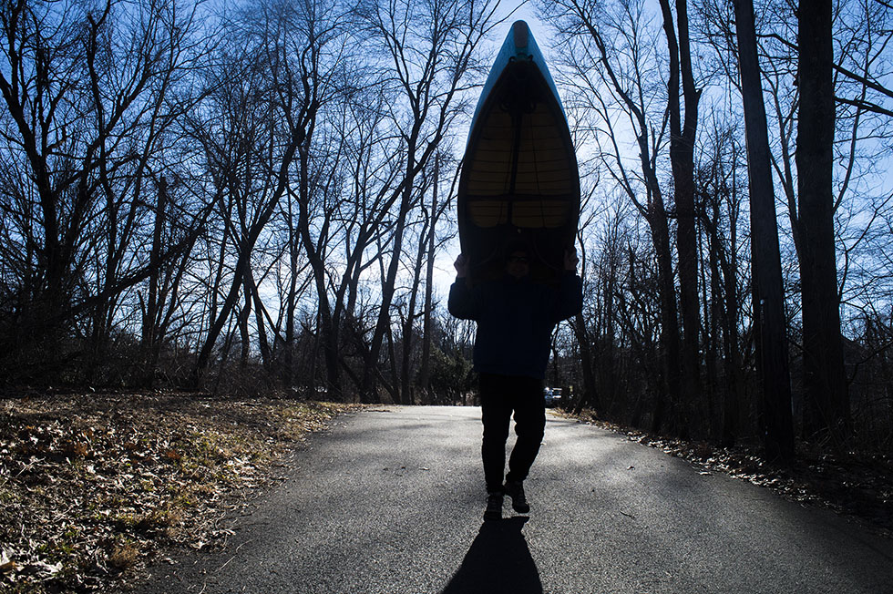 "01.01.2015 - Tariffville, Ct.. - Erik Eckilson of Woonsocket, Rhode Island, walks to the shores of the Farmington River before paddling with 14 other boaters as part of a ""New Year's tradition."" ""To have a good year, if you're a whitewater boater, you have to be in the water on the first,"" said participant Ian Scott of Branford, Ct. Photograph by Mark Mirko 