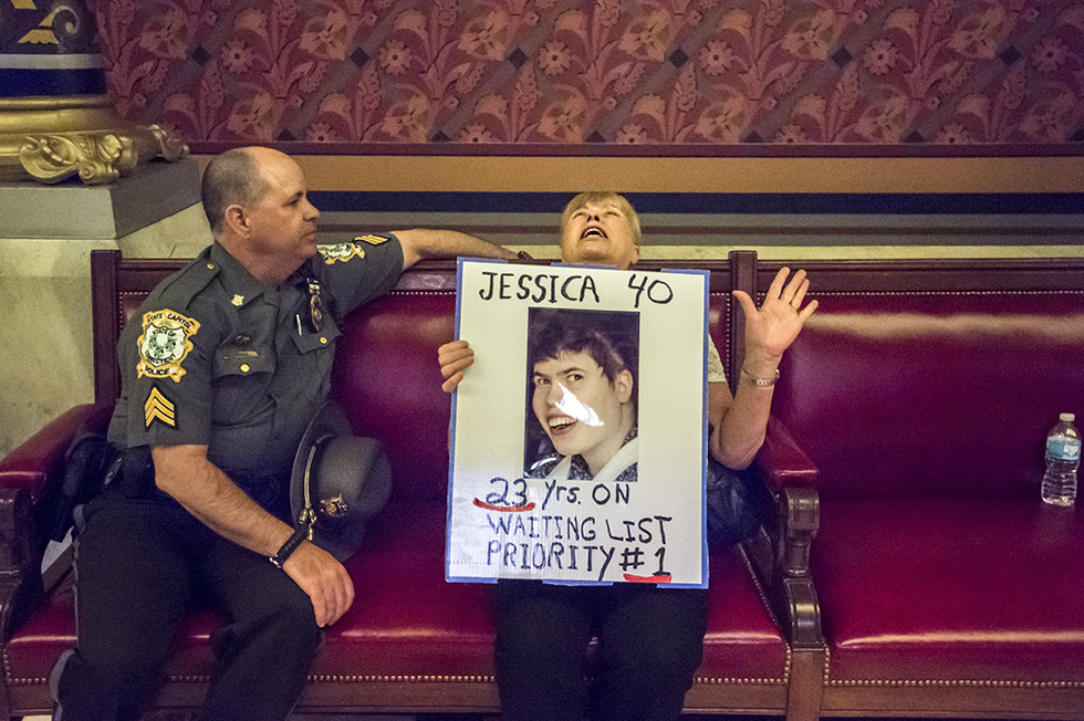 "05.06.2015 - Hartford, Ct. - Proclaiming, ""Arrest me, I don't care,"" 68-year-old Heddy Castelano sits outside the chambers of the Connecticut House of Representatives expressing her frustration with proposed budget cuts to the Department of Developmental Services. Moments earlier, Barter ordered Castelano and over 100 others gathered outside the chambers, relocate as the House came to session. Castelano's daughter, Jessica, is 40-years-old, developmentally delayed and suffers from a seizure disorder. And has been on a DDS waiting list for residential services for 23-years. Castelano came to the capitol today, with hundreds of others, to gathering outside of the Hall of the House to show support for people with disabilities, mental health issues and poverty. ""We're here to facilitate people participating in the process. Not deprive them of their rights,"" said Barter. Photograph by Mark Mirko 