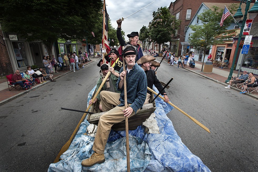 "07.04.2015 - Willimantic, Ct. - Replicating ""Washington Crossing the Delaware"" by artist Emanuel Leutze, Steven Sweeney, dressed as a sword-wielding George Washington, stands in the middle of a boat pulled on a trailer during the Boom Box Parade in Willimantic. The Boom Box parade is an annual July 4th tradition for Willimantic started in 1986, after a marching band could not be found for Windham's Memorial Day Parade. Local radio station WILI plays music on the air, while people march and watch, playing their radios. Photograph by Mark Mirko 