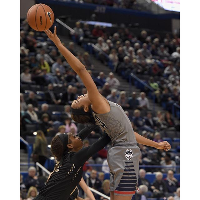 Connecticut Huskies guard/forward Napheesa Collier (24) is stretches to the limit for a pass as UCF Knights forward Nyala Shuler (12) puts an arm into her back during the second half  at the XL Center in Hartford Wednesday night in Hartford. Collier scored 14 points and grabbed 7 rebounds in a 101-51 victory. Photo by JOHN WOIKE | woike@courant.com