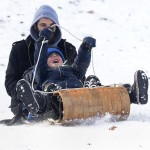 """""""It's all in the steering,"""" says Nosson Rich who toboggans down the popular sledding hill at Elizabeth Park in Hartford on Monday afternoon with his sons Menachen Rich, 6, and Avraham, 2, (obcured by Menachen. Rich says he shoveled snow for four hours yesterday at their home in Teaneck, New Jersey before driving to Connecticut to visit family.  PATRICK RAYCRAFT 