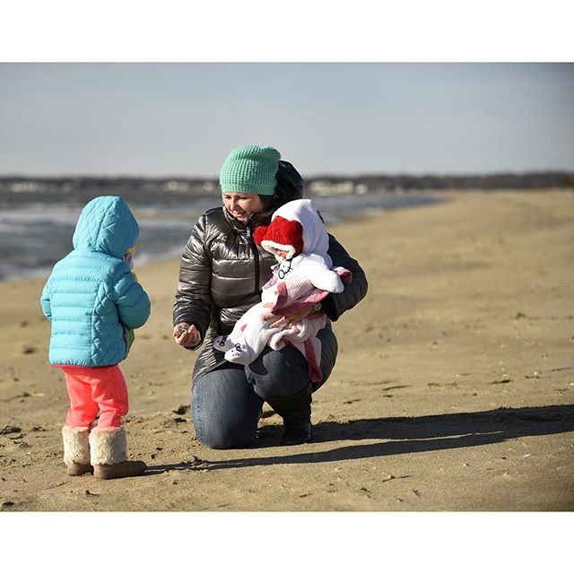 """Renata Wawszkiewicz, of Bristol, shows her daughter, Olivia, 2, a shell she found on the beach while holding Olivia's little sister, Kamila, 7 months, at Hammonasset Beach State Park Wednesday.  The Wawszkiewiczes stopped at the beach to get some fresh air after going to a doctors appointment nearby. """"I've been coming here since I was a kid and we camp here every summer,"""" said Wawszkiewicz. """"I just love the beach."""" CLOE POISSON