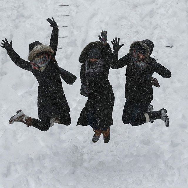 Women jump as they pose for a picture while visiting Central park as snow falls on January 23, 2016 in New York.  A deadly blizzard with bone-chilling winds and potentially record-breaking snowfall slammed the eastern US on Saturday, as officials urged millions in the storm's path to seek shelter -- warning the worst is yet to come. US news reports said at least eight people had died by late Friday from causes related to the monster snowstorm, which is expected to last until early Sunday. / AFP / KENA BETANCURKENA BETANCUR/AFP/Getty Images