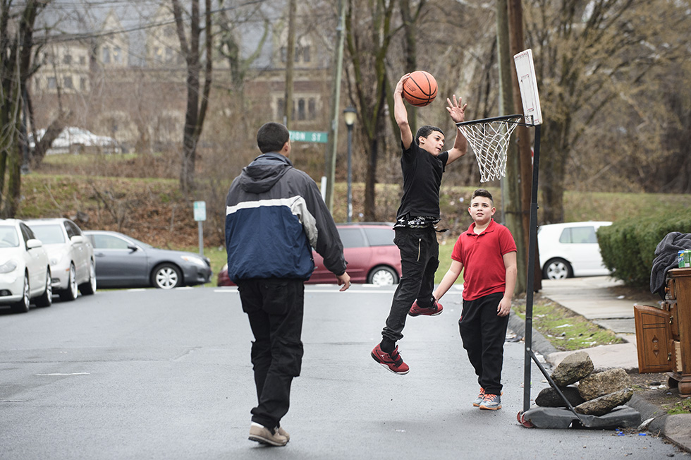03.28.2016 - Hartford, Ct. - Kevin Garcia (middle) dunks on a basketball hoop while playing with his brother-in-law David Velasquez (left) and friend Kedrick Luciano (right) Garcia says he set up the hoop today after rolling it home from a neighbor's house where it had been thrown away. Garcia, who says he plays on the basketball and baseball teams at his school, also said it just took a few rocks to steady the base and the hoop was ready to go. Photograph by Mark Mirko | mmirko@courant.com