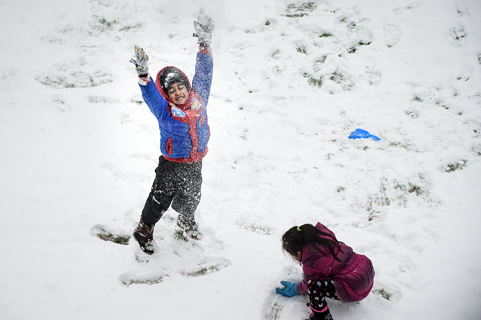 """04.04.2016 - Mansfield, Ct. - Pretending to be """"a bulldozer, and the snow is exploding,"""" Chanithu Bodhipakasha throws fresh snow into the air while playing in the day's snowfall with his friend Nancy Niu. Schools closed today in Mansfield because of the storm that dropped 1-3 inches overnight. Said Niu about being home from school today,  """"I'm happy but kind os sad that I can't learn anything."""" (Cq on both names) Photograph by Mark Mirko 
