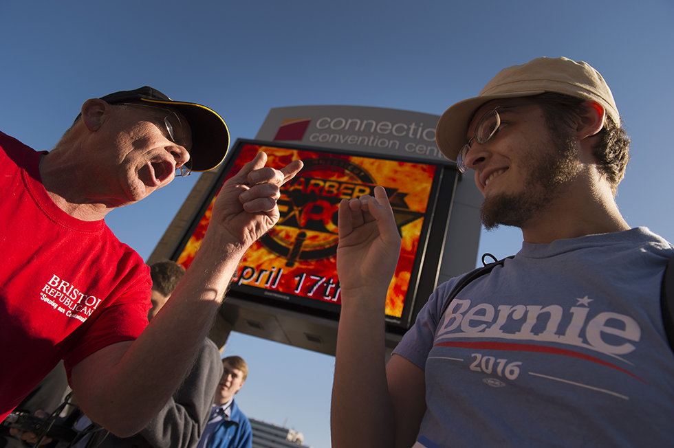 "04.15.2016 - Hartford, Ct. - Cliff Carlson, a republican and undecided voter, argues with ""L,"" a Bernie Sanders supporter, before Trump's rally. Photograph by Mark Mirko. 