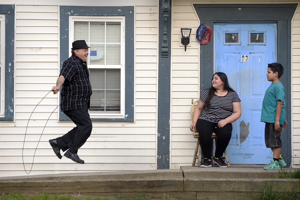 04.18.2016 - Willimantic, Ct. - 67-Year-old Pedro Morales plays with a jump rope he borrowed from Marivelisse Lopez, 12, and her brother Edwin Lopez, 12, on the front porch of their Willimantic home. Photograph by Mark Mirko | mmirko@courant.com