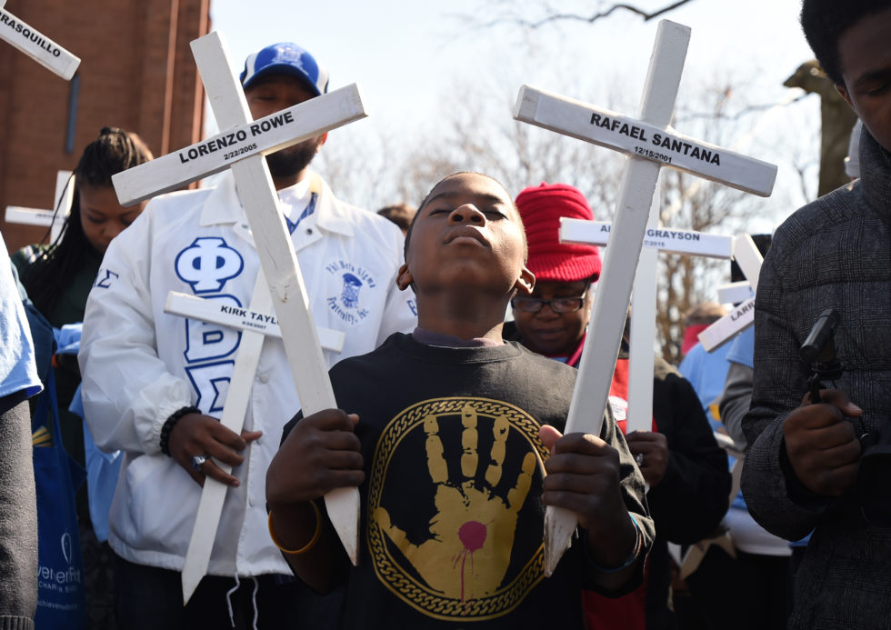Hartford, CT - 4/16/16 - Mothers United Against Violence organized the 8th Annual March and Memorial Rally Saturday. Here, Noble Moody, of East Windsor, listens during a prayer before the March began at the corner of Albany Avenue and Main Street. Marchers hold crosses that represent 2015 fallen Hartford victims of violence. The event coincides with National Crime VictimsÕ Rights Week. Photo by BRAD HORRIGAN | bhorrigan@courant.com