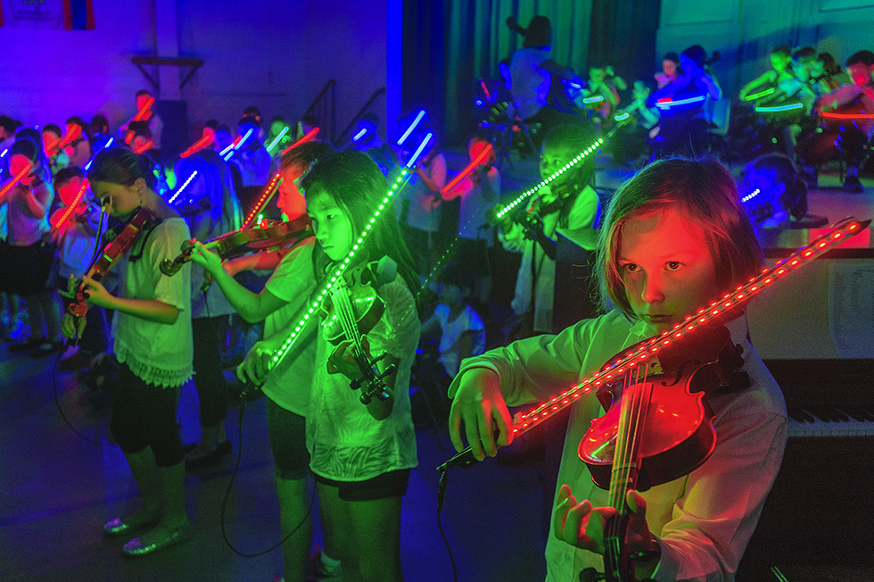 """Mansfield, CT, 5/16/2016 - Their bows lit with LED lights, seventy students in the Mansfield Public Schools Suzuki String Program perform the theme from Star Wars at Annie E. Vinton school while on an end-of-the-year tour of the town's three elementary schools. Suzuki violin teacher Barbara Vaughn said the idea to light bows like light sabres started after student Brendan Kaufold asked if  they could """"take a vacation from"""" the standard Suzuki songs during their one-day three-school concert. The Suzuki program in Mansfield has been touring their town's elementary schools since 1979. Photo by Mark Mirko 